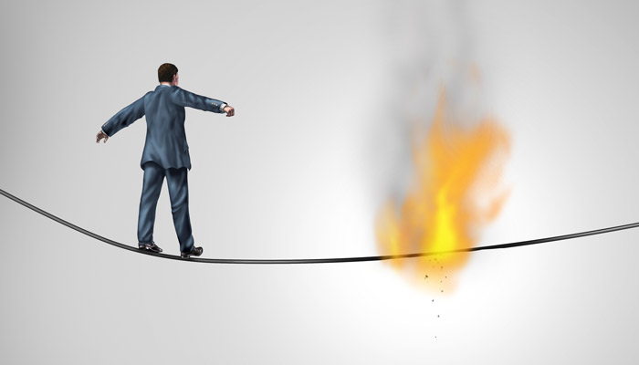 A man walking a rope that is on fire because he didn't know the new hazards that he could walk into